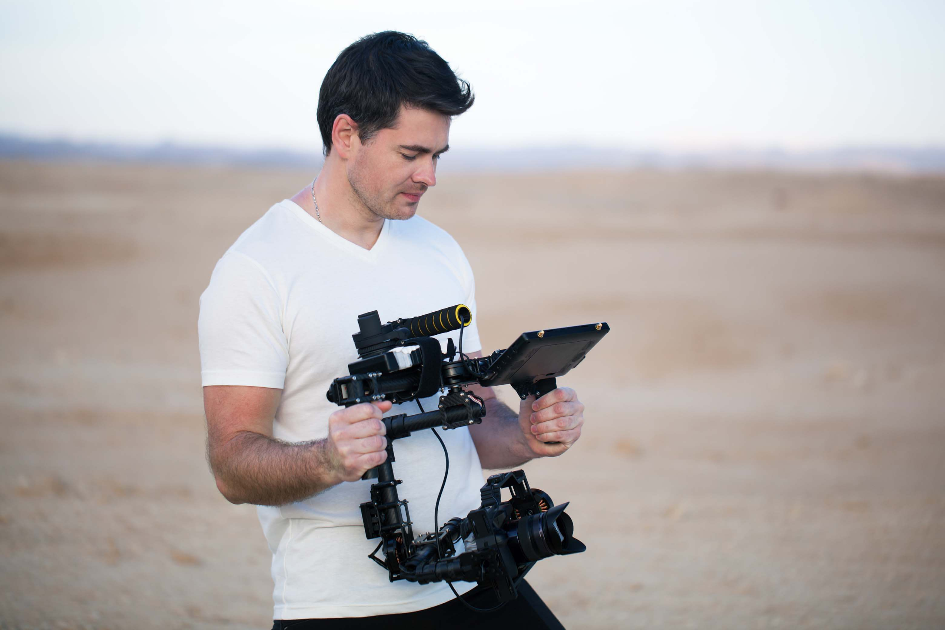 Young videographer shooting on the beach using steadycam. He looking at result on display